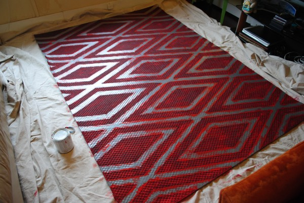 I put a drop cloth under the rug and put on 2 coats of paint, letting it dry overnight between coats.
